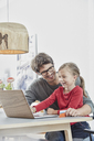Happy father and daughter with a card using laptop on table at home - RORF01169