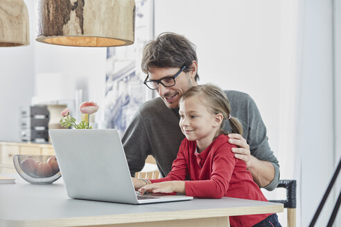 Smiling father and daughter using laptop on table at home - RORF01172