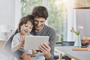Happy father and son using tablet at home together - RORF01178