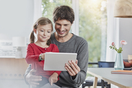 Smiling father and daughter using tablet at home together - RORF01181