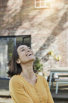 Portrait of happy woman in front of her home - RORF01193
