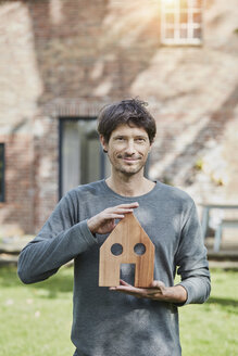 Portrait of smiling man in front of his home holding house model - RORF01196