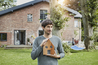 Portrait of man in garden of his home holding house model - RORF01199