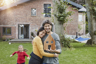 Portrait of smiling couple with daughter in garden of their home holding house model - RORF01202