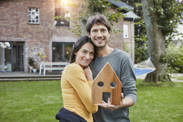 Portrait of smiling couple in garden of their home holding house model - RORF01205
