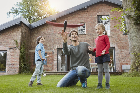 Father with two children playing with toy airplane in garden of their home - RORF01208