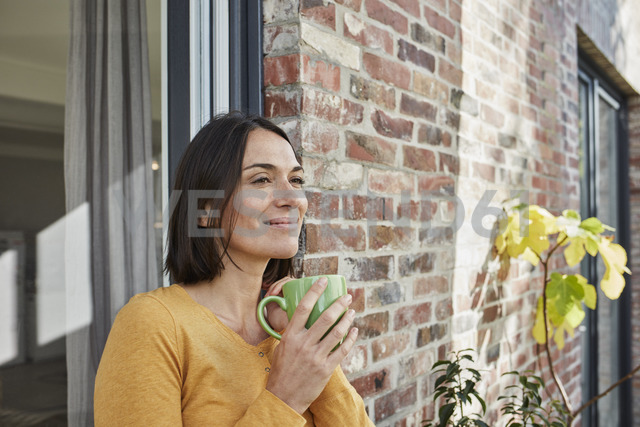 Smiling woman drinking from cup in front of her home - RORF01214 - Roger Richter/Westend61