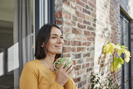 Smiling woman drinking from cup in front of her home - RORF01214