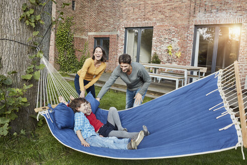 Happy family playing in hammock in garden of their home - RORF01217