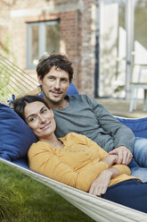 Smiling couple lying in hammock in garden of their home - RORF01220