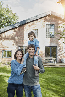 Portrait of happy family with son in garden of their home - RORF01226