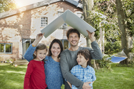 Portrait of happy family in garden of their home holding roof - RORF01229