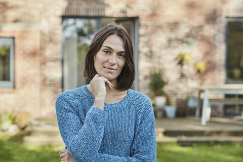 Portrait of confident woman in garden of her home - RORF01235