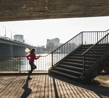 Young woman running towards stairs at a river - UUF13054