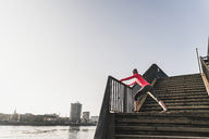 Young woman stretching on stairs at a river in the city - UUF13057