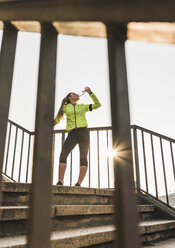 Sportive young woman standing on stairs drinking from bottle - UUF13063