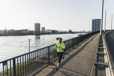 Young woman running on bridge at the riverside - UUF13066