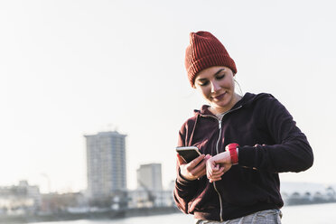 Sportive young woman at the riverside in the city with smartphone and smartwatch - UUF13069