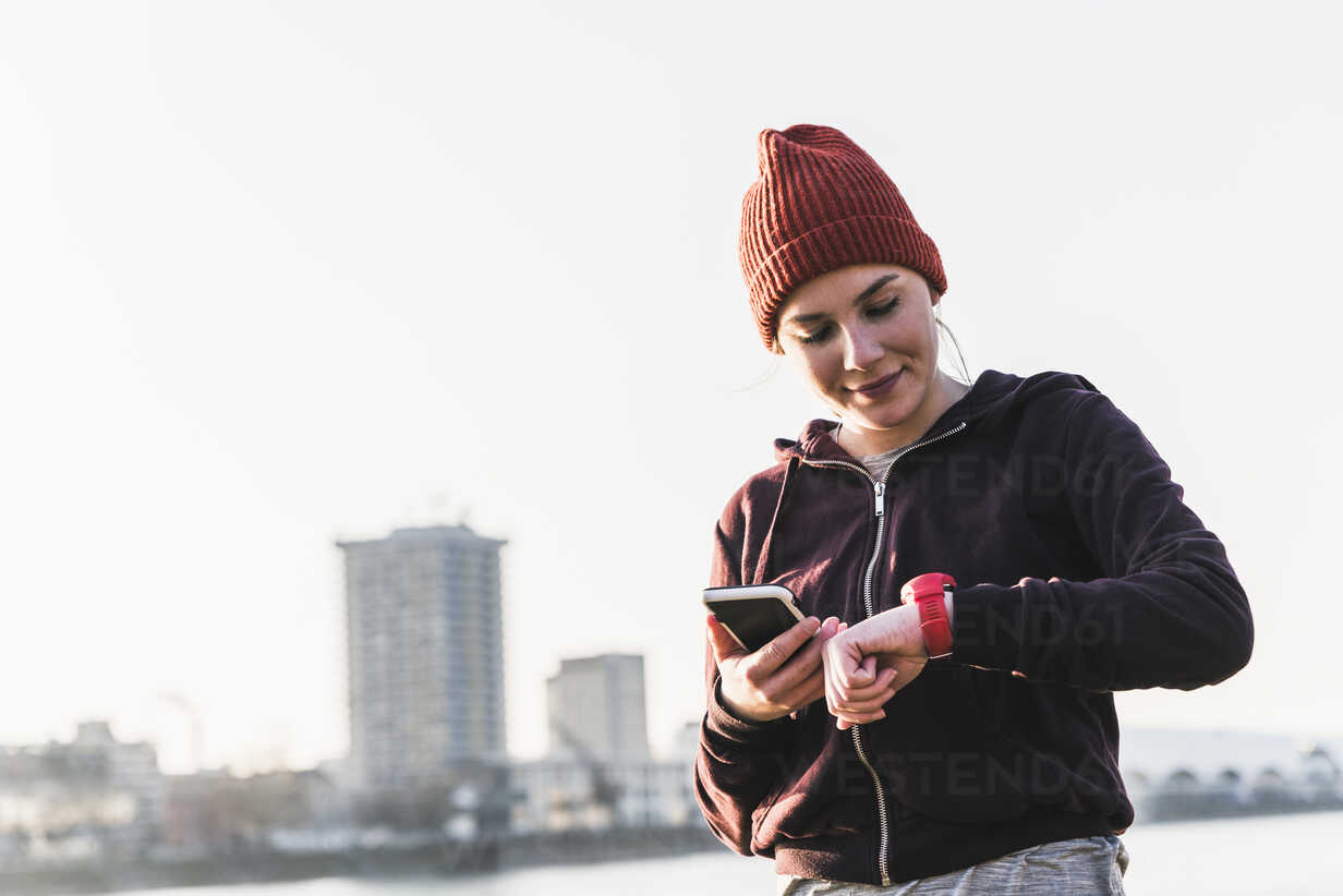 Sportive young woman at the riverside in the city with smartphone and smartwatch - UUF13069 - Uwe Umstätter/Westend61