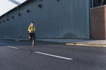 Young woman running on a street - UUF13072
