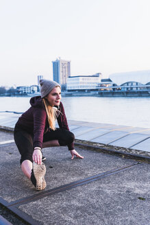 Young woman stretching at the riverside in the city - UUF13081