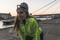 Sportive young woman with headlamp at dusk at the riverside in the city - UUF13084