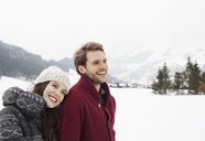 Happy couple in snowy field - CAIF12347