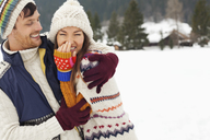 Couple laughing and hugging in snowy field - CAIF12350