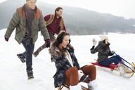 Enthusiastic friends sledding in snowy field - CAIF12362