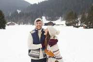 Couple hugging and laughing in snowy field - CAIF12365