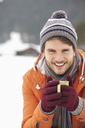 Close up portrait of smiling man in knit hat and gloves drinking coffee in snowy field - CAIF12368