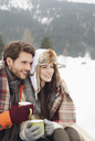 Happy couple drinking coffee in snowy field - CAIF12374