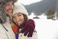 Close up portrait of happy couple hugging in snowy field - CAIF12377