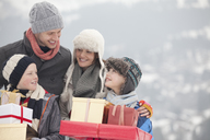 Happy family carrying Christmas gifts in snow - CAIF12398