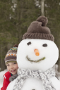Portrait of smiling boy behind snowman with stocking-cap - CAIF12428