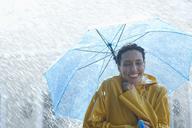 Happy woman under umbrella in rain - CAIF12443