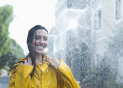 Enthusiastic woman standing in rain - CAIF12446
