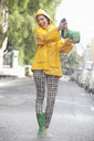 Portrait of enthusiastic woman emptying boot in rain - CAIF12449