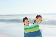 Girls wrapped in towel on beach - CAIF12455