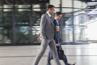 Corporate businessmen with coffee walking outside building - CAIF12476