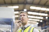 Supervisor using walkie-talkie in steel factory - CAIF12548