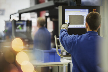 Worker at control panel in steel factory - CAIF12617