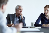 Attentive senior businessman listening to businesswoman in meeting - CAIF12623