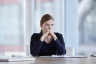Pensive businesswoman looking away in conference room - CAIF12647