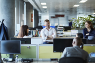 Business people talking in office cubicle - CAIF12674