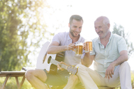 Father and adult son toasting beer mugs and playing guitar outdoors - CAIF12680