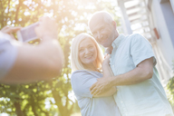 Man photographing senior couple outdoors - CAIF12683