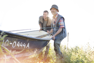 Father and adult son lifting fishing boat - CAIF12686