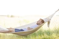 Young man sleeping in summer hammock - CAIF12689