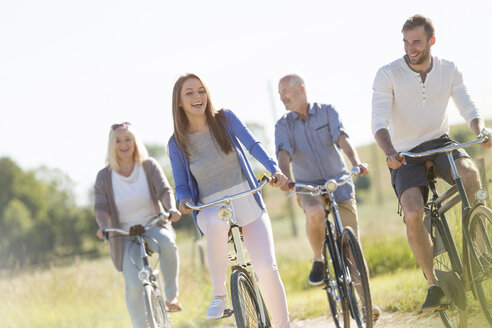 Happy family bike riding in sunny field - CAIF12698